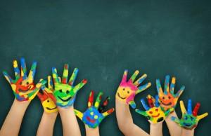 bunte Kinderhände vor Schultafel